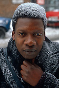 A man of Afro-Caribbean birth, clutches at his scarf to keep out freezing temperatures during a cold snap in south London. Falling snow has settled on the man's black hair and even turned his eyelashes white after his walk from home to a local bus stop from where he is trying to commute to work. Because of skin colour, the white snowflakes make this picture a largely monochrome scene, adding to the bleak sense of wintry conditions. He is clearly unprepared for winter, wearing neither hat nor gloves and looks chilled to the bone thanks to the heat he's losing through his head and upper body. The climate of this part of the northern hemisphere can be ferocious for those ill-equipped or at the very least, unpleasant for those from warmer parts of the world.