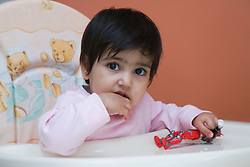 Young boy; sitting in a high chair; playing with a toy,