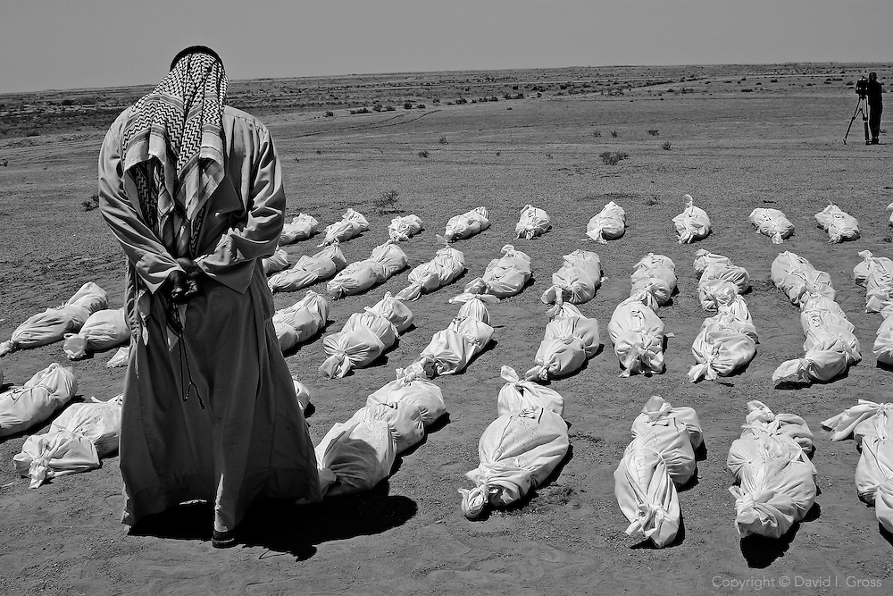An array of shroud-wrapped remains lie in the desert at a mass grave near Al-Musayab, Iraq.