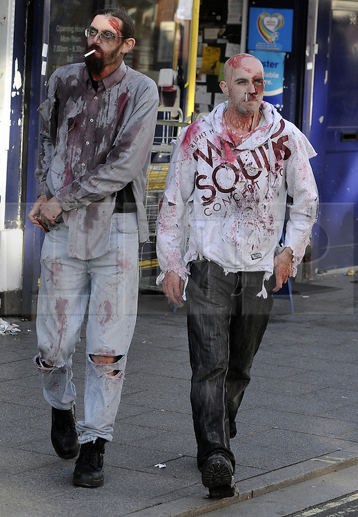 """© Licensed to London News Pictures. 15/09/2013<br /> Cigarette break for two zombies.<br /> Brentwood zombie movie """"Welcome to Essex""""<br /> The final shoot of  Welcome to Essex  has seen 1500 zombies running down Brentwood High Street this morning (15.09.2013) on the last day of filming for one of the biggest low-budget horror films.<br /> The film follows  Ryley Dunn played by Catherine Delaloye who after a drunken fall that lands her unconscious wakes up to find Brentwood over run with Zombies...<br /> Photo credit :Grant Falvey/LNP"""