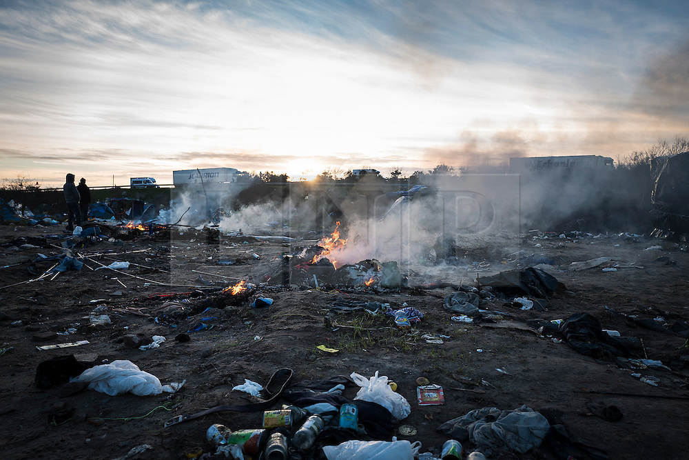 © London News Pictures. 18/01/16. Calais, France. Fires burn in an Afghan section of the Calais 'Jungle' which has been cleared ahead of a planned eviction. French authorities are to bulldoze a 100-metre 'buffer zone' between the camp and the adjacent motorway, which leads to the ferry port.Photo credit: Rob Pinney/LNP