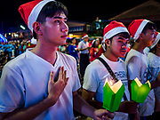 "23 DECEMBER 2018 - CHANTABURI, THAILAND: High school students make the ""sign of the cross"" at the Cathedral of the Immaculate Conception's Christmas Fair in Chantaburi. Cathedral of the Immaculate Conception is holding its annual Christmas festival, this year called ""Sweet Christmas @ Chantaburi 2018"". The Cathedral is the largest Catholic church in Thailand and was founded more than 300 years ago by Vietnamese Catholics who settled in Thailand, then Siam.   PHOTO BY JACK KURTZ"