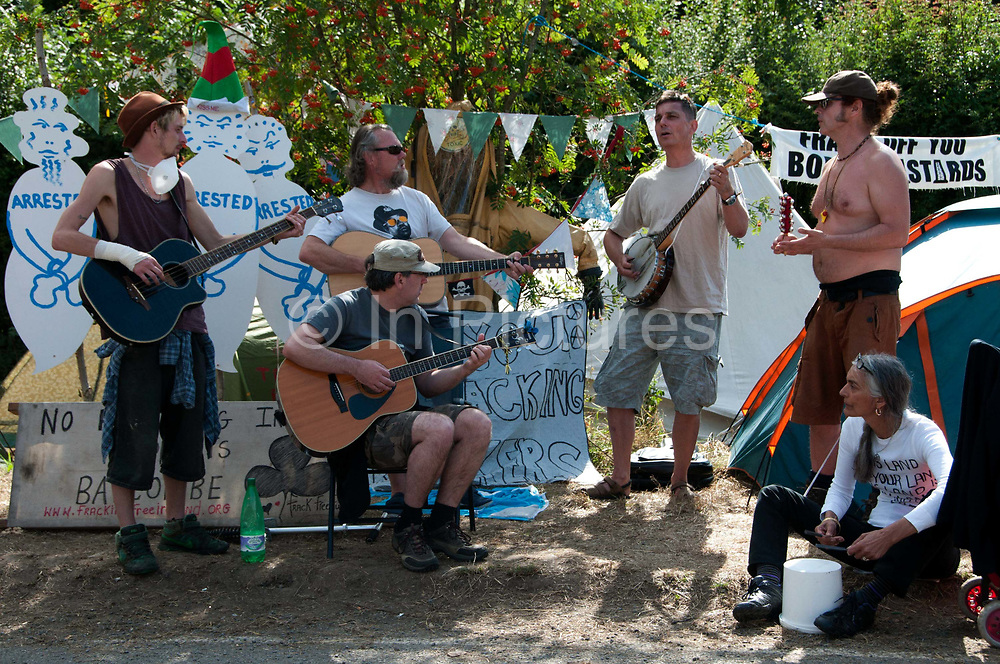 Balcombe, West Sussex. Site of Cuadrilla drilling . Roadside camp of protesters. A group of musicians sing protest songs in front of cardboard cutout figures of arrested protesters.