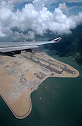 A Singapore Airlines Boeing 747-400 Jumbo flies over the construction site of Chek Lap Kok Airport on Lantau island during approach to Kai Tak.