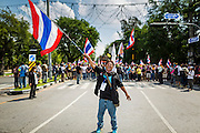 26 NOVEMBER 2013 - BANGKOK, THAILAND: A Thai anti-government protestor waves a Thai flag and screams at riot police in Bangkok. Protestors opposed to the government of Thai Prime Minister Yingluck Shinawatra spread out through Bangkok this week. Protestors have taken over the Ministry of Finance, Ministry of Sports and Tourism, Ministry of the Interior and other smaller ministries. The protestors are demanding the Prime Minister resign, the Prime Minister said she will not step down. This is the worst political turmoil in Thailand since 2010 when 90 civilians were killed in an army crackdown against Red Shirt protestors. The Pheu Thai party, supported by the Red Shirts, won the 2011 election and now govern. The protestors demanding the Prime Minister step down are related to the Yellow Shirt protestors that closed airports in Thailand in 2008.     PHOTO BY JACK KURTZ
