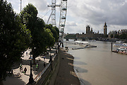 A low-tide River Thames, people on Millennium Walk, London Eye, and the Houses of Parliament are seen from a high viewpoint.
