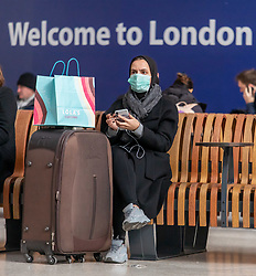 © Licensed to London News Pictures. 12/03/2020. London, UK. A train travellers at Victoria Station wears a masks as the World Health Organization declares Covid19 the Coronavirus disease a Pandemic and US President Donald Trump bans all travel from Europe except the UK as fears over the Coronavirus continues. Photo credit: Alex Lentati/LNP
