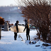 """Aurelien sees a friend and fellow member of the Rochester Surf Club, Darell Licata, while walking back to his vehicle. Aurelien is originally from France. """"I never thought I would find waves on the Great Lakes that I could surf!"""""""
