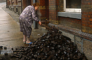 Six months after the fall of the Berlin Wall, a lady shovels East German Lignite coal briketts left outside her home, on 1st June 1990, in Aue, Saxony, eastern Germany (former DDR). The coal was delivered as Briketts and was either Lignite or Braunkohle, imported from either Poland or northern Czech Republic.