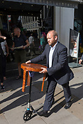 A man pushes a small scooter that supports a wooden three-legged table, on 1st September 2017, in London, England.