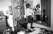 As her younger brother makes mischief in the background, 4 year-old girl looks at her appearance in front of a large mirror in her own bedroom at home in south London. In her own private play world, the girl uses a soft brush and looks at herself in the large mirror and she stands on her bed strewn with a girl's fluffy toy characters including a 'Raggedy Ann' and a rabbit. In the background is a naughty little brother who has been searching for something in his sister's cupboard.
