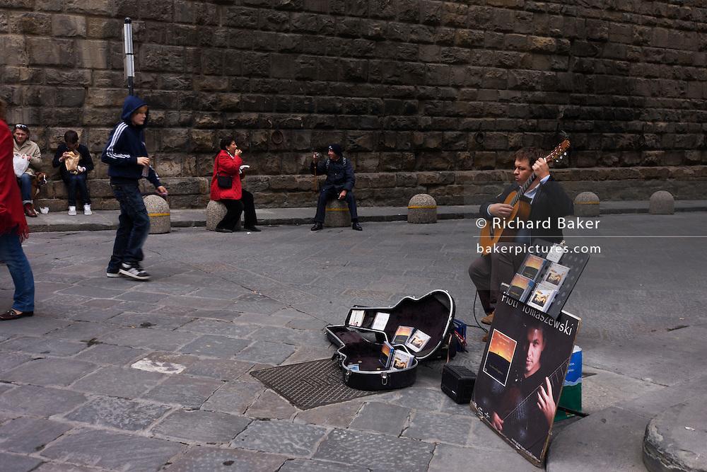 Classical guitarist plays totourists in Florence's Piazza degli Uffizi