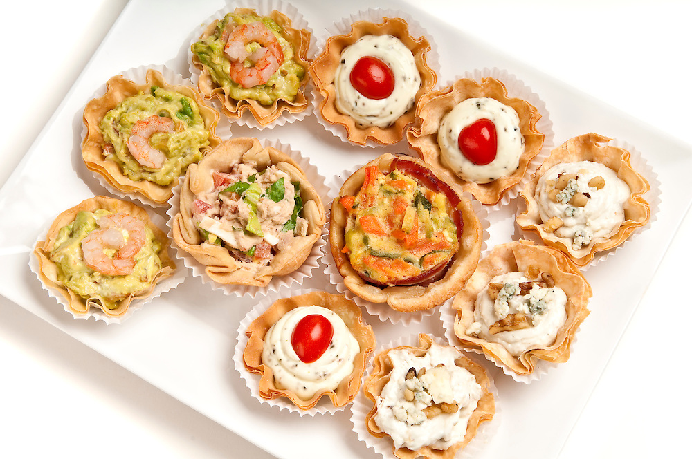 Tray full of volauvent canapes ready to serve. Volauvent is a tiny round canapé made of puff pastry. The term ' vol au vent ' means ' blown by the wind ' in French.