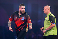Michael Smith celebrates with Michael van Gerwen looking on during the 2019 William Hill World Darts Championship Final at Alexandra Palace, London, United Kingdom on 1 January 2019.