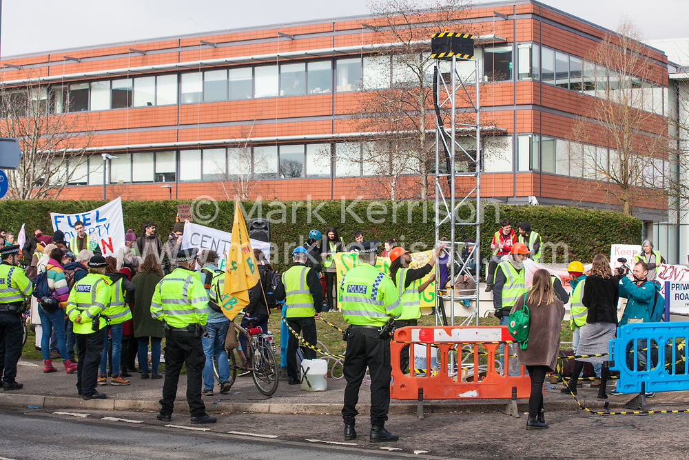 Windsor, UK. 22nd February, 2019. Around 60 campaigners from Reclaim the Power and Fuel Poverty Action set up a mock fracking site during a family-friendly protest outside the headquarters of Centrica to call on the British multinational energy and services company to cease its support for fracking operations through its partnership with shale gas company Cuadrilla Resources. Security guards and around 50 Thames Valley Police officers were deployed around the Centrica headquarters.