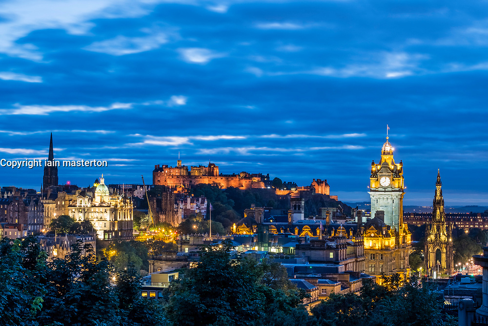 View of famous Edinburgh skyline with the castle to rear at dusk in Edinburgh, Scotland, United Kingdom.