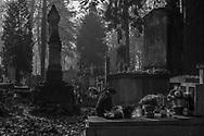 A elderly woman remembers her deceased loved ones at Rakowicki Cemetery in Krakow, Poland 2019.