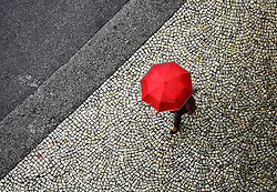 April 7, 2017 - Sao Paulo, Brazil - A woman with a red umbrella walks along the sidewalk on another rainy day in Sao Paulo, with mild temperatures in the Valley of the Anhangabau region.  (Credit Image: © Aloisio Mauricio / Fotoarena via ZUMA Press)
