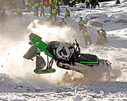NEWS&GUIDE PHOTO / PRICE CHAMBERS<br /> Todd Tupper's snowmobile sheds parts on impact as it tumbles down Snow King mountain on Saturday. The Hailey, Idaho rider was thrown from the sled as he neared the top of the 4,000 foot course that claimed many costly machines over the weekend.