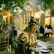 Patrons at a restaurant. Surrounded by desert, the city of Yazd is famous for its architecure, its wind towers and its traditional zoroastrian community of fire worshippers.  <br /> <br /> Travelling over 4000km by train across Iran. An opportunity to enjoy Persian hospitality, discover Iran's ancient cities and its varied landscapes, from deserts to mountains.