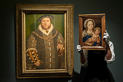 """© Licensed to London News Pictures. 04/12/2015. London, UK. A technician holds """"Mabuse"""" by Jan Gossaert (est. £4-6 million) whilst standing next to """"Portrait of Henry VIII"""" by Hans Holbein (est. £0.8-1.2 million), ahead of Sotheby's London evening sale of Old Master and British paintings on 9th December 2015. This king's painting is the last official image of his reign.  Photo credit : Stephen Chung/LNP"""