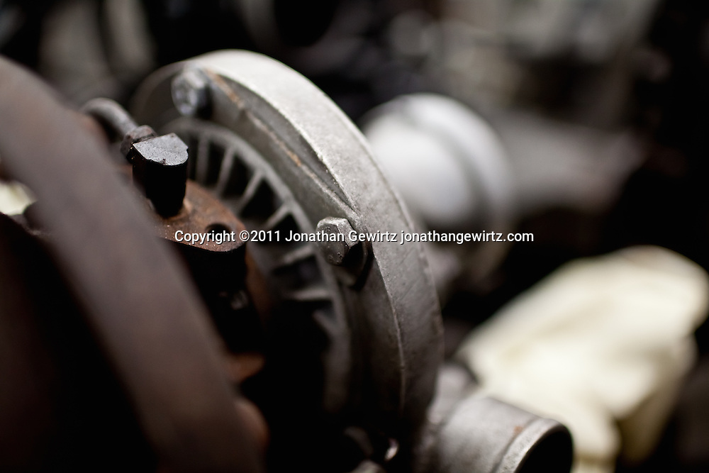 Close up view of metal parts in an old car engine.