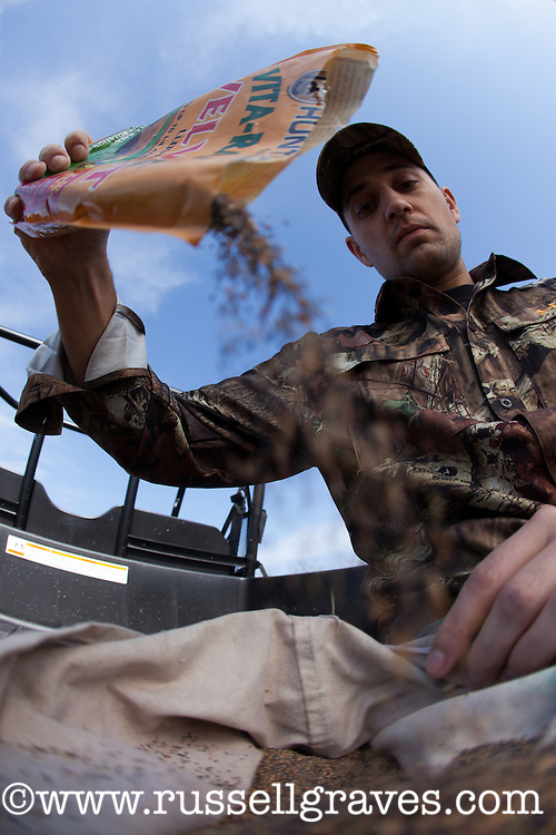 DEER HUNTER POURING FOOD PLOT SEED INTO A BROADCAST SEEDER