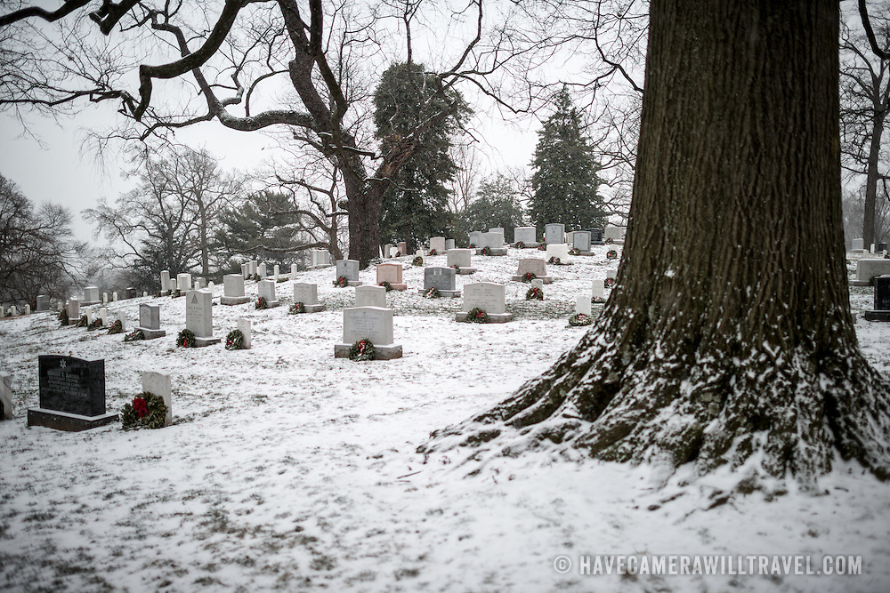 The ground of Arlington National Cemetery is covered in a light blanket of snow after recent snowfall.