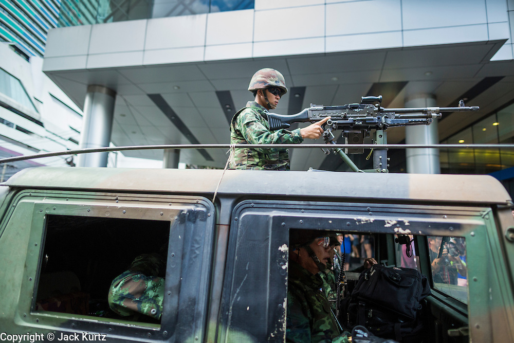 """01 JUNE 2014 - BANGKOK, THAILAND: A Thai soldier in an armed humvee arrives at Terminal 21, a Bangkok shopping mall, to put down a protest in the mall. The Thai army seized power in a coup that unseated a democratically elected government on May 22. Since then there have been sporadic protests against the coup. The protests Sunday were the largest in several days and seemed to be spontaneous """"flash mobs"""" that appeared at shopping centers in Bangkok and then broke up when soldiers arrived. Protest against the coup is illegal and the junta has threatened to arrest anyone who protests the coup. There was a massive security operation in Bangkok Sunday that shut down several shopping areas to prevent the protests but protestors went to malls that had no military presence.    PHOTO BY JACK KURTZ"""