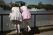 "Two girls wearing Lolita dresses lean over the barrier over the River Thames on the South Bank, London, UK. Lolita fashion is a subculture originating in Japan that is based on Victorian-era clothing. The look began primarily as one of modesty with a focus on quality with a sense of the gothic also. The original shape is a knee length skirt with a ""cupcake"" shape assisted by petticoats, but has expanded into various types of garments. Blouses, knee high socks or stockings and headdresses are also worn."