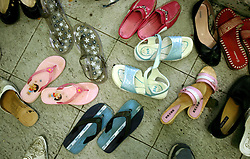 Shoes of mothers and their girls collect outside the site where a mass circumcision will take place in Bandung, Indonesia on April 23, 2006. The families of 248 girls were given money to have their children circumcised in a mass circumcision celebration timed to honour the Prophet Mohammed's birthday. While religion was the main reason for circumcisions, it is believed by some locals that a girl who is not circumcised would have unclean genitals after she urinates which could lead to cervical cancer. It is also believed if one prays with unclean genitals their prayer won't be heard. The practitioners used scissors to cut the hood and tip of the clitoris. The World Health Organization has deemed the ritual unnecessary and condemns such practices.