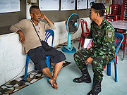 15 AUGUST 2016 - BANGKOK, THAILAND: TAWATCHAI VORAMAHAKUN, left, a community historian and leader in the Pom Mahakan slum, talks to a Royal Thai Army NCO while city officials served eviction notices to residents of the slum. Final eviction notices were posted today and residents of the slum have been told they must leave the fort by September 3, 2016. Residents have indicated that they don't want to leave the area and Tawatchai has become a spokesman for those who want to stay. The Pom Mahakan community is known for fireworks, fighting cocks and bird cages. Mahakan Fort was built in 1783 during the reign of Siamese King Rama I. It was one of 14 fortresses designed to protect Bangkok from foreign invaders. Only two of the forts are still standing, the others have been torn down. A community developed in the fort when people started building houses and moving into it during the reign of King Rama V (1868-1910). The land was expropriated by Bangkok city government in 1992, but the people living in the fort refused to move. In 2004 courts ruled against the residents and said the city could take the land.      PHOTO BY JACK KURTZ