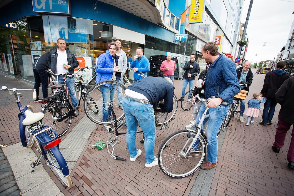 In Utrecht kijkt een groep vrienden lachend toe hoe een van hun zijn fiets repareert omdat de ketting eraf ligt.<br /> <br /> In Utrecht a group of friends watch one of them fixing his bicycle.