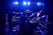 Drummer Matt Letley of Status Quo plays drums under blue lights on stage during European tour at L'Aeronef in Lille, France.