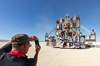 Duane captures his mutant vehicle Rabid Transit at Reared In Steel's Fire Kethedral by: Reared In Steel from: Petaluma, CA year: 2019<br /> <br /> The Fire Kethedral will resemble a cathedral organ as a colossal fire instrument – a shrine to fire. The structure will be fabricated from steel tubing and CNC cut sheet metal standing forty feet tall and fifty feet long. The Fire Kethedral will be an ornate and powerful instrument capable of choreographing fire as music through a full keyboard as an instrumentalist plays sitting on an ornately decorated piano bench. Pipes mounted into the structure will shoot fire up into the air coordinated with every keystroke. The Kethedral will be adorned with stained glass lighted by flame rail pilots creating a tabernacle of fire and light. LED lighting will amplify the visual effect of the fire and sound.