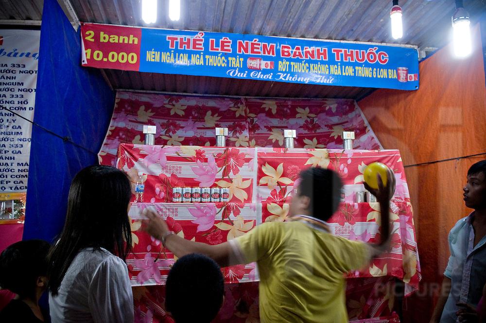 A vietnamese man tries to break some cans in a funfair stall. Nha Trang Vietnam, Asia