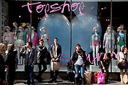 Shoppers gather outside Topshop in central London on Oxford Street. UK. Topshop is a mid range retail outlet.
