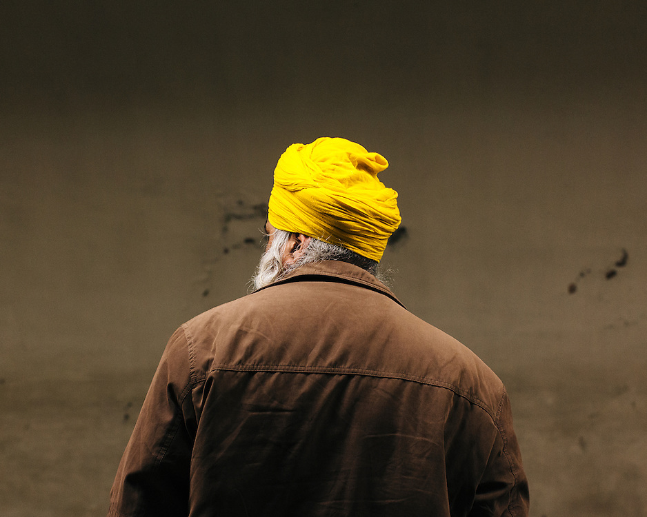 A sheikh man with yellow turban seen from behind