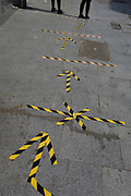 The day after UK Prime Minister Boris Johnson addressed the nation with his roadmap for the coming weeks and months during the Coronavirus pandemic lockdown, the feet and legs of two south London women stand on the now worn hazard tape that marks out safe social distancing practice at East Street Market on the Walworth Road, on 11th May 2020, in London, England.