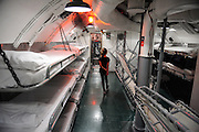 8 year old child in crew sleeping quarters of WW2 submarine, the USS Bowfin. USS Bowfin Submarine Museum and Park, part of the USS Arizona Memorial Museum in Pearl Harbour, Hawai.