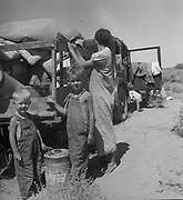 America in the Great Depression, 1936. Destitute family of nine, about to to sell their trailer and their belongings to raise cash to buy food.