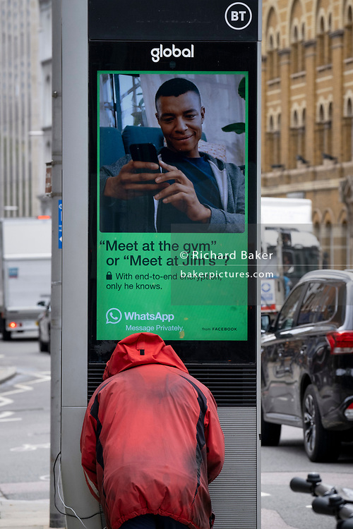 A rear, anonymous view of a homeless man who is using a BT charging point that advertises WhatsApp, in SE1, on 22nd June 2021, in London, England.
