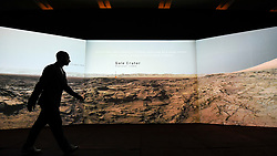 "© Licensed to London News Pictures. 17/10/2019. LONDON, UK. A staff member walks in front of a video projection showing the view on Mars from the Curiosity rover. Preview of ""Moving to Mars"" at the Design Museum. The exhibition explores how sending humans to Mars is a frontier for science as well as design and features over 200 exhibits from NASA, the European Space Agency together with new commissions.  The show is open 18 October to 23 February 2020.  Photo credit: Stephen Chung/LNP"