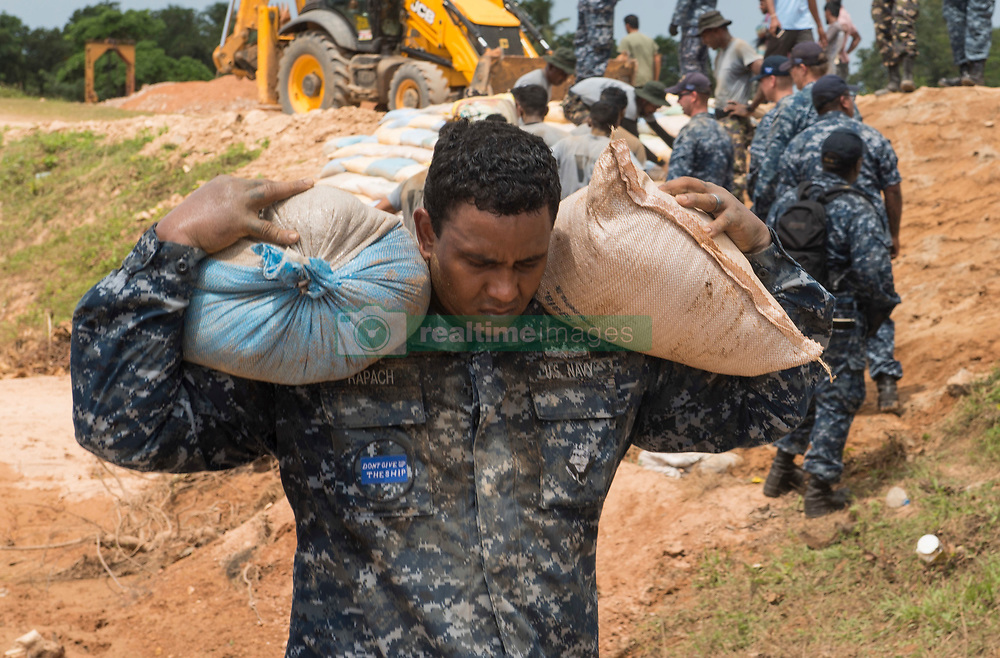 June 12, 2017 - Matara, Sri Lanka - U.S. Navy sailors from the Ticonderoga-class guided-missile cruiser USS Lake Erie work alongside Sri Lankan Marines to repair levees damaged in severe flooding and landslides June 12, 2017 in Matara, Sri Lanka. More than 600,000 were forced from their homes by monsoon rains killing over 200 and leaving thousands stranded. (Credit Image: © Joshua Fulton/Planet Pix via ZUMA Wire)