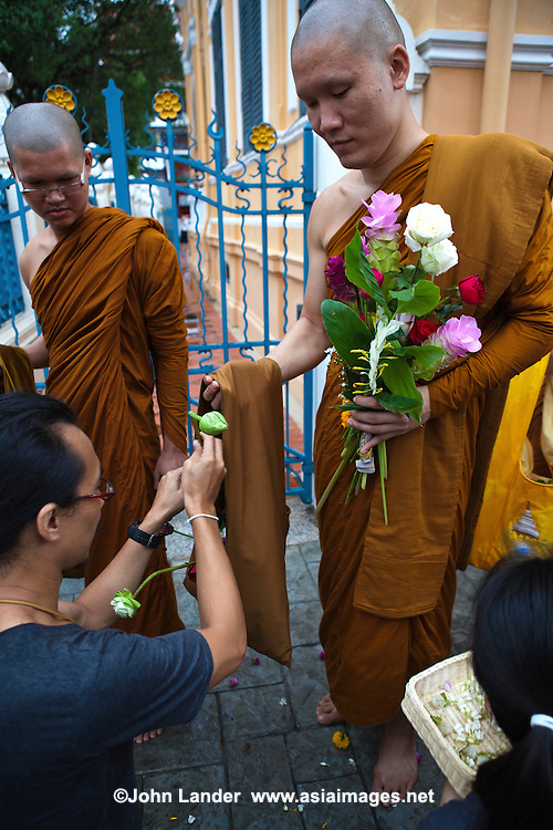"""Marking the beginning of the three month Buddhist Lent,  monks go on retreat during this time to practice meditation.  To mark the beginning of this period, many temples organize offerings of giant candles to the monks, while other temples have processions where worshippers offer flowers. The classic flower offered is """"dancing lady ginger"""" globba winitti."""
