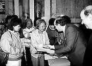 Justice Minister Gerard Collins TD presents a large group of Vietnamese refugees with certificates of naturalisation at the Department of Foreign Affairs in Iveagh House. The group of 156 adults, dispossessed due to the Vietnam war, arrived in Ireland from Vietnam and some refugee camps in Hong Kong and Malaysia.<br />