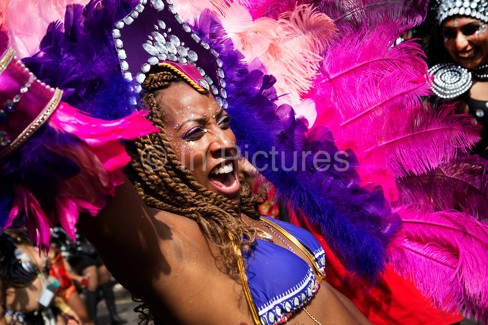 Notting Hill Carnival August 28th 2017. West London, England. A very happy carnival dancer wearing a pink and purple feather head dress shouts with delight.