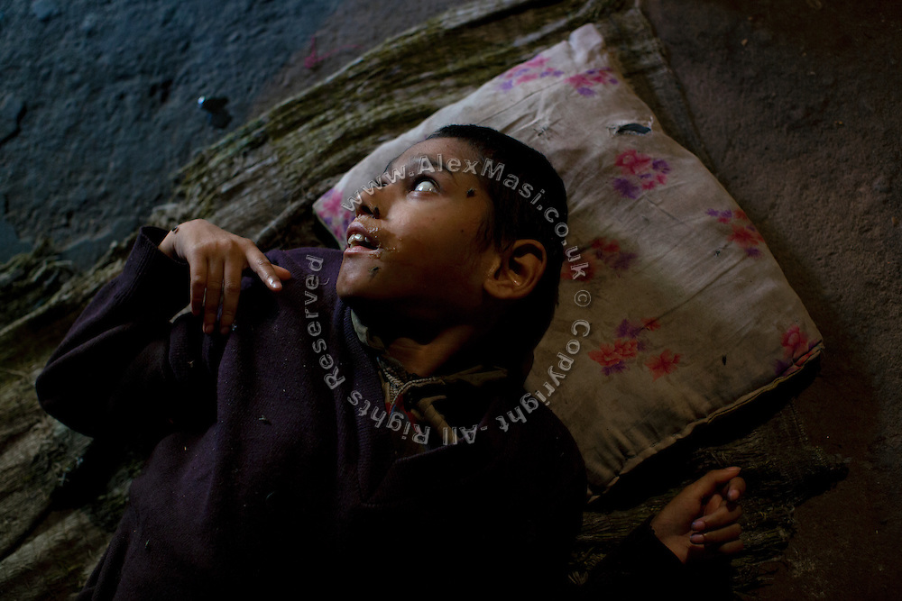 Samir, 14, a severely disabled boy, is looking towards the light outside while lying on the floor of his home in Kasi Camp, one of the water-affected colonies standing near the abandoned Union Carbide (now DOW Chemical) industrial complex, site of the infamous 1984 gas tragedy in Bhopal, Madhya Pradesh, central India. The poisonous cloud that enveloped Bhopal left everlasting consequences that today continue to consume people's lives.