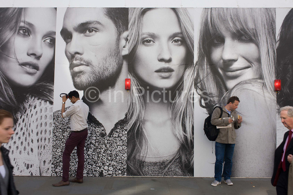 As two passers-by walk into the city scene, two more Londoners stand beneath the panels of a large poster for the H&M clothing brand on Regent Street, London. The faces of female and one male model look out towards the street in the shopping area north of Oxford Circus where many branded shops line Regent Street. Modelling affordable street fashion we see young, beautiful people represented on the billboard, their clothes all perfect and stylish while the realities of ordinary folk are below.