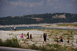 Vacationers walking on the Sometimes Islands at Lake Travis in Austin, Texas
